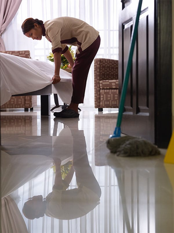 Hotel cleaning staff making bed